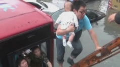A baby is rescued from a trapped bus in flooded east China