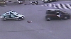 The child falls out of the car on a busy road.
