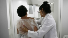 A woman undergoes a mammogram.