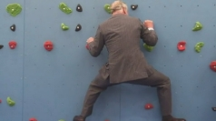 Prince Charles attempts a climbing wall in Jersey.