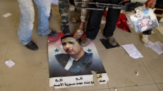 Rebels stomp on a picture of Assad.