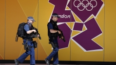 Armed policemen walk past an Olympic logo.