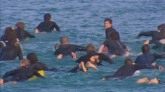 Ring of surfers: A tribute to a shark attack victim