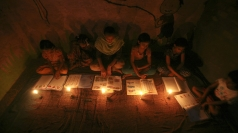 Children study by candlelight in New Delhi.