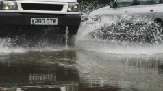 A van drives through flood water.