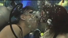 Couples kiss underwater.