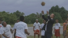 Prince William throws coconuts with locals.