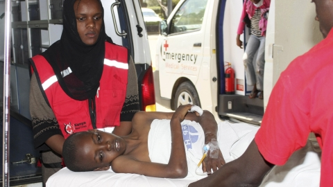 Kenya Red Cross personel assist injured child after blast