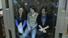 Three members of Pussy Riot seated in a glass cage in court