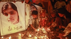 Children light oil lamps near a picture of Malala Yousufzai.