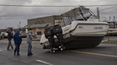 Residents photograph a boat as they inspect damage.