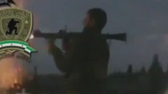 A rebel fighter fires a rocket-propelled grenade at the base