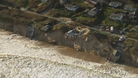 Tidal surge batters UK coast and drags homes into the sea
