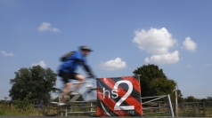 A man cycles past an anti high speed rail project sign.